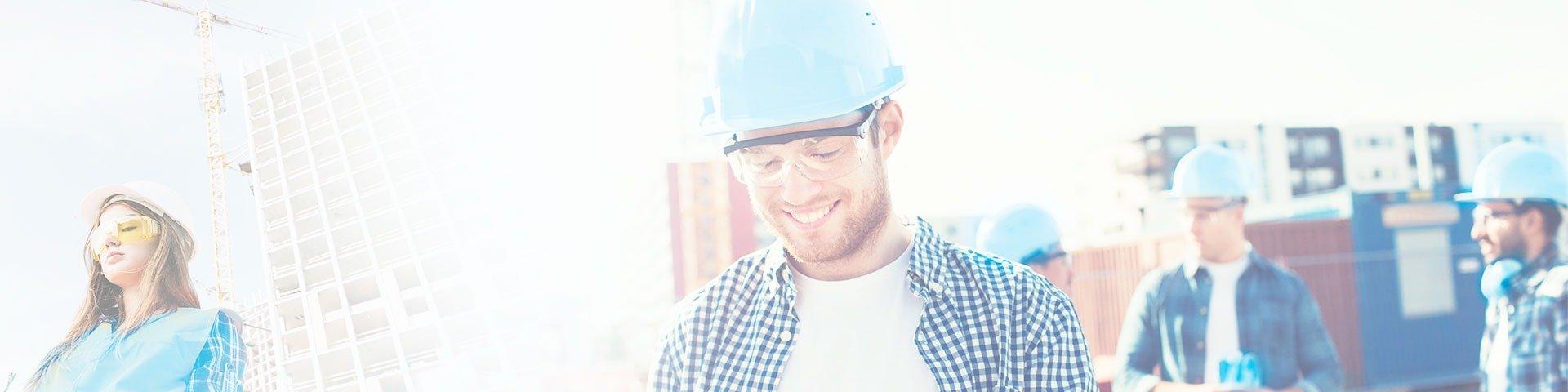 trabalhador sorridente com capacete azul e grua ao fundo