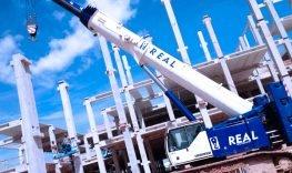 Guindaste da real guindaste com lança aberta em operação próximo a grande fábrica em construção