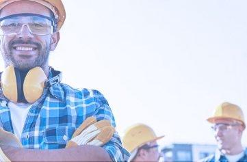 trabalhe na real - funcionários em frente obra com capacetes de segurança
